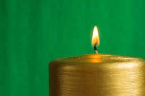 Burning gold candle on a green background